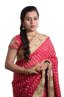 Jovem mulher bonita que levanta no saree tradicional indiano no branco.