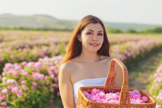 Jovem mulher bonita que levanta perto das rosas em um jardim.