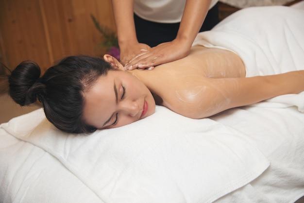 Jovem mulher bonita que obtém o salão de beleza da massagem dos termas.