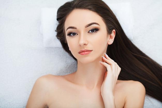 Jovem mulher bonita que obtém um tratamento da cara no salão de beleza.