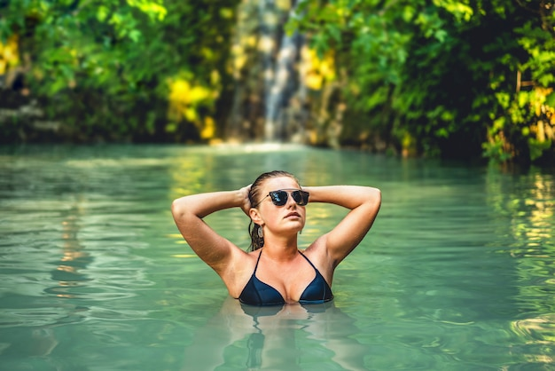 Jovem mulher bonita que relaxa no lago da caverna da selva