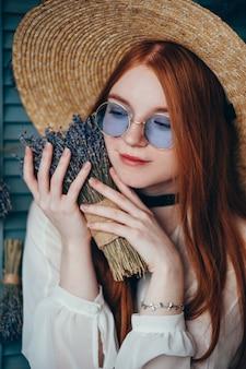 Jovem mulher bonita que senta-se com alfazema contra a parede azul.