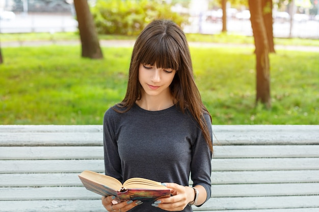 Jovem mulher bonita que senta-se em um banco na rua que lê um livro.
