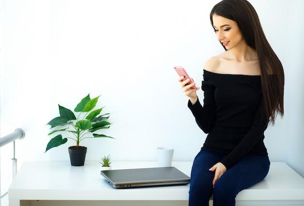 Jovem mulher bonita que senta-se em uma mesa com um dobrador e um telefone.
