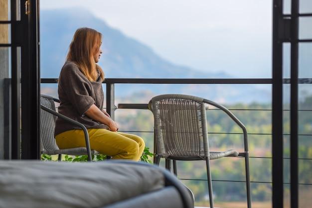 Jovem mulher bonita que senta-se no balcão do hotel do quarto para apreciar a opinião da paisagem do nascer do sol.