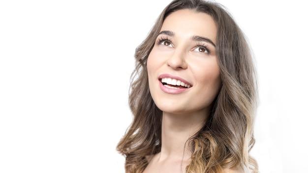 Jovem mulher bonita que sorri, dentes saudáveis brancos, pele limpa.