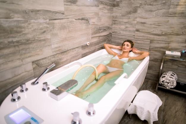Jovem mulher bonita recebe hidromassagem e tratamentos médicos para relaxamento no centro médico spa moderno