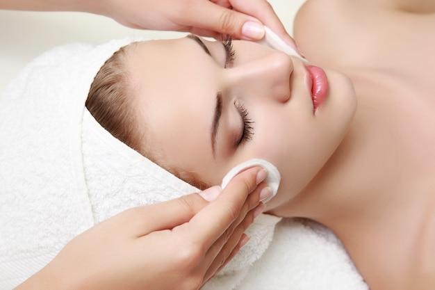 Jovem mulher bonita recebendo massagem facial e tratamento de spa