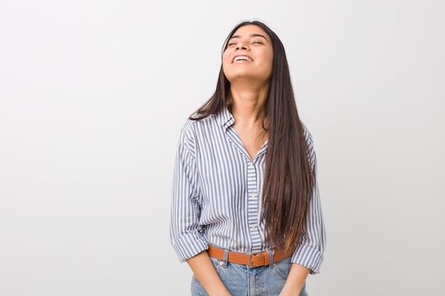 Jovem mulher bonita relaxada e feliz rindo, pescoço esticado, mostrando os dentes