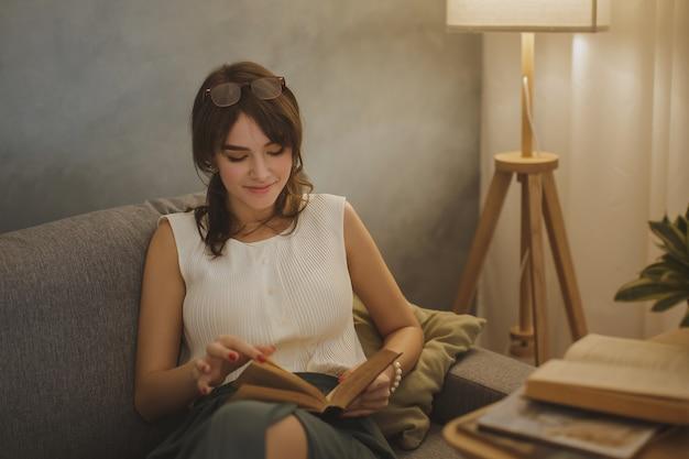 Jovem mulher bonita relaxando em casa à noite aconchegante e lendo o livro.
