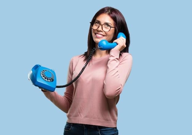 Jovem mulher bonita rindo alto, se divertindo com a conversa, chamando um amigo ou um cliente