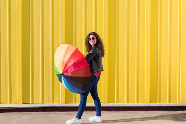 Jovem mulher bonita se divertindo com um guarda-chuva colorido sobre amarelo. estilo de vida.