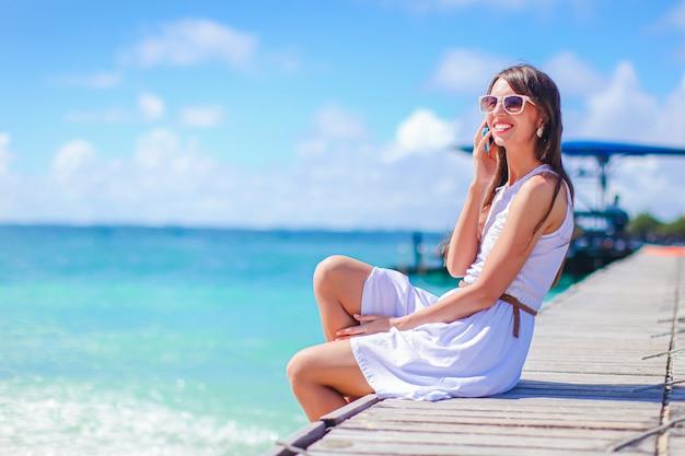 Jovem mulher bonita se divertindo na beira-mar tropical. menina feliz o céu azul e a água turquesa no mar na ilha do caribe