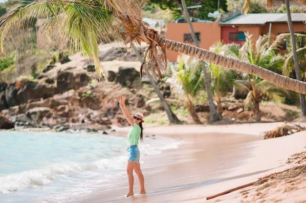 Jovem mulher bonita se divertindo na beira-mar tropical.