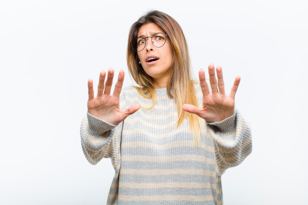 Jovem mulher bonita se sentindo aterrorizada, recuando e gritando de horror e pânico, reagindo a um pesadelo contra a parede branca