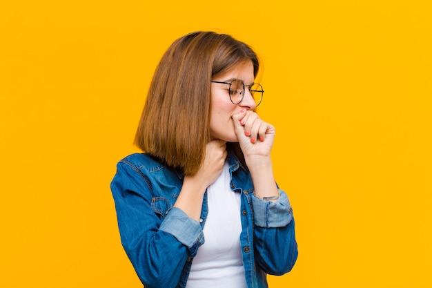Jovem mulher bonita se sentindo doente com sintomas de dor de garganta e gripe, tossindo com a boca coberta contra a parede amarela