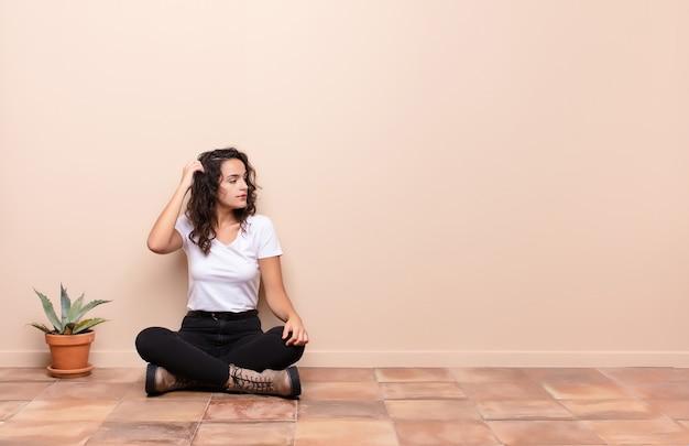 Jovem mulher bonita se sentindo sem noção e confusa, pensando uma solução, com a mão na anca e outra na cabeça, vista traseira, sentado no chão do terraço