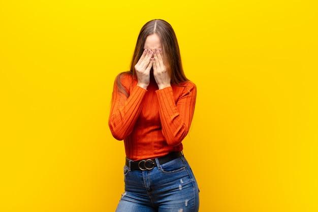 Jovem mulher bonita se sentindo triste, frustrada, nervosa e deprimida, cobrindo o rosto com as duas mãos, chorando contra laranja