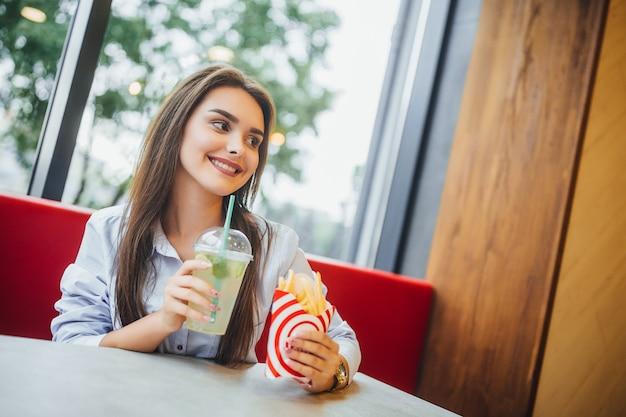 Jovem mulher bonita segurando hambúrguer e mohito no restaurante de fast food