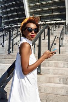 Jovem mulher bonita segurando o telefone subindo escadas