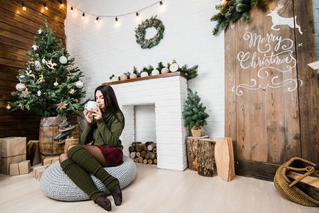 Jovem, mulher bonita, segurando um copo com uma bebida quente com árvore de natal no fundo