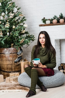 Jovem, mulher bonita, segurando um copo com uma bebida quente