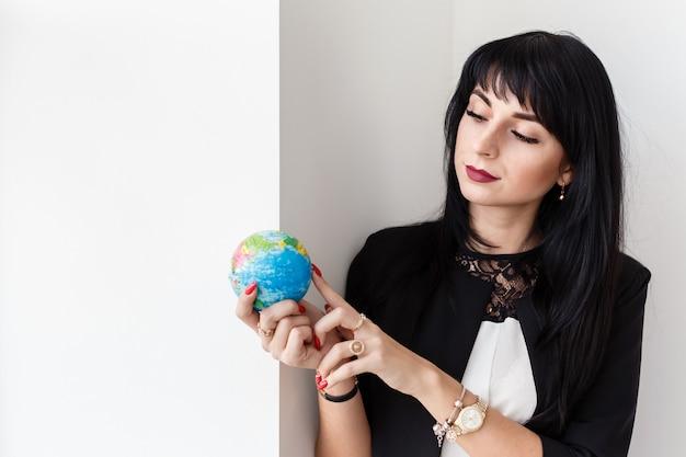 Jovem mulher bonita segurando um globo do planeta terra.