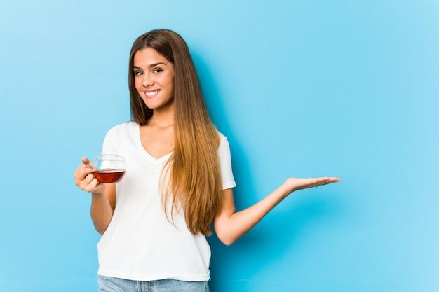 Jovem mulher bonita segurando uma xícara de chá mostrando um na palma da mão e segurando a outra mão na cintura.