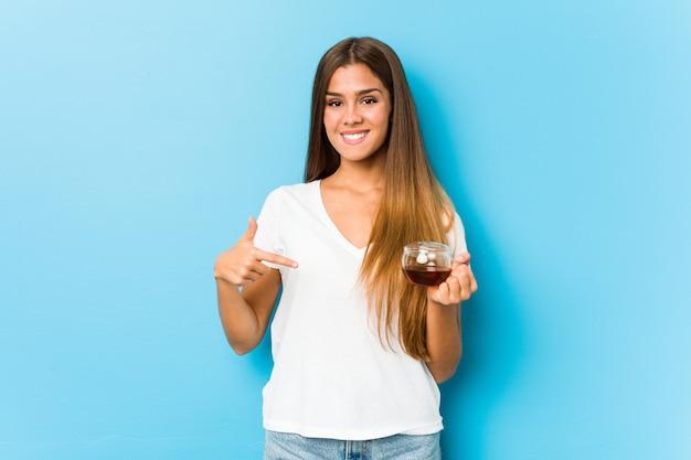 Jovem mulher bonita segurando uma xícara de chá pessoa apontando à mão para um espaço em branco da camisa