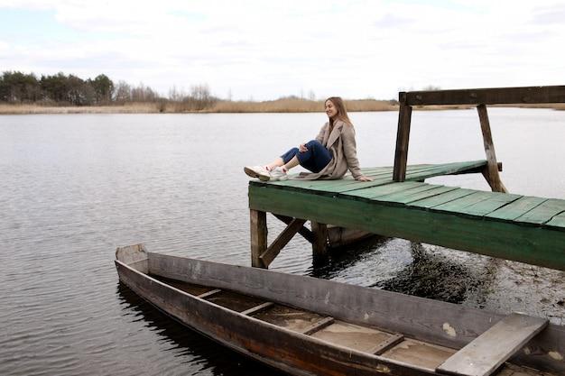 Jovem mulher bonita senta-se na ponte de madeira no rio em dia de primavera. barco velho perto da costa. foco seletivo.