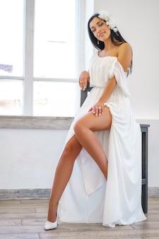 Jovem mulher bonita sentada na cadeira no vestido branco