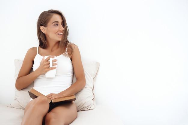 Jovem mulher bonita sentada na cama, bebendo chá, lendo o livro