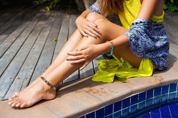 Jovem mulher bonita sentada na piscina com um vestido boho amarelo, tendência da moda do verão, sexy, magra, pele bronzeada, pernas magras, férias tropicais, hotel resort, detalhes