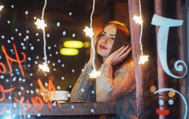 Jovem mulher bonita sentada no café, bebendo café. modelo ouvindo música. natal, ano novo, dia dos namorados, férias de inverno