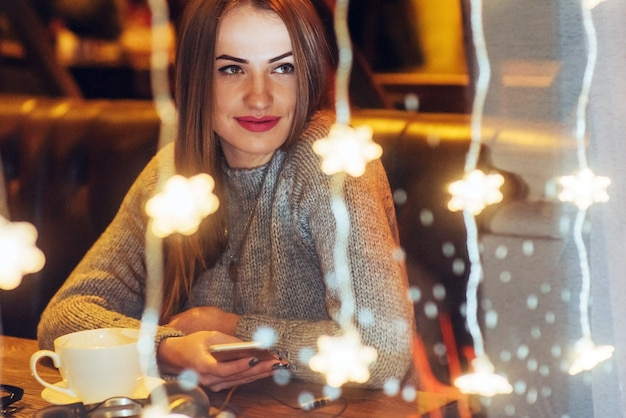Jovem mulher bonita sentada no café, bebendo café. natal, ano novo, dia dos namorados, férias de inverno