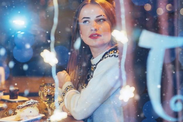 Jovem mulher bonita sentada no café, bebendo vinho. natal, ano novo, dia dos namorados, férias de inverno