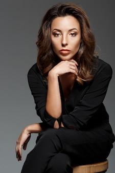 Jovem mulher bonita sentada sobre parede cinza
