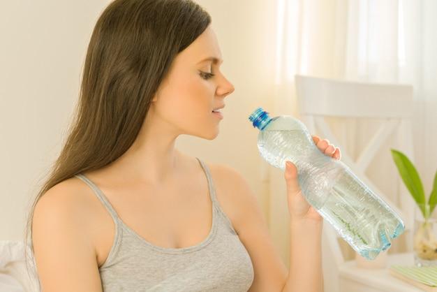 Jovem, mulher bonita, sentando, casa, em, cama, bebendo, mineral, água, de, garrafa