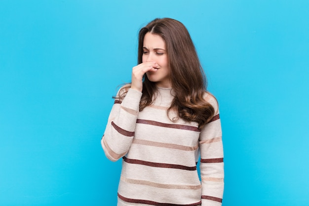 Jovem mulher bonita sentindo nojo, segurando o nariz para evitar cheirar um fedor sujo e desagradável sobre parede azul