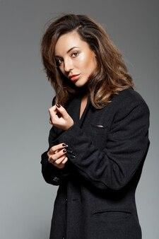 Jovem mulher bonita sobre parede cinza
