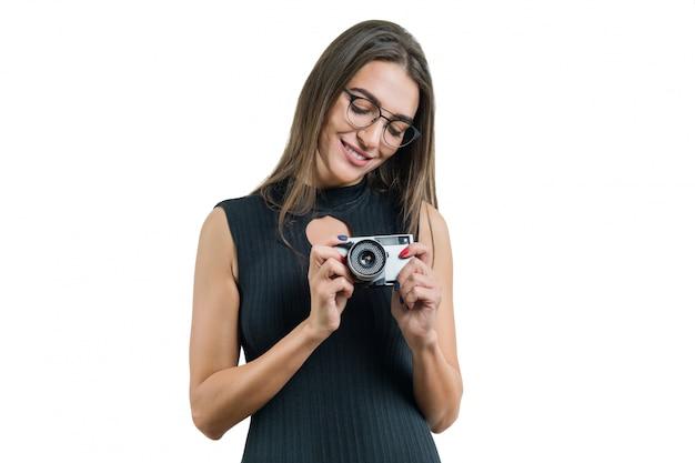 Jovem mulher bonita sorridente em óculos de vestido preto, segurando a câmera fotográfica nas mãos dela