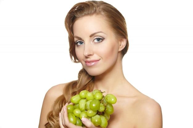 Jovem mulher bonita sorridente sexy segurando um cacho de uva nas mãos com cabelos longos, isolado no branco