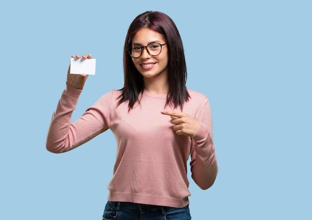 Jovem mulher bonita sorrindo confiante, oferecendo um cartão de visita, tem um negócio próspero