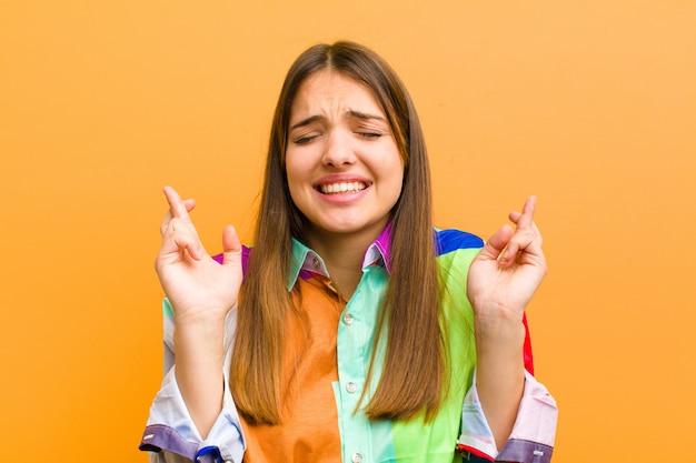 Jovem mulher bonita sorrindo e cruzando ansiosamente os dois dedos, sentindo-se preocupada e desejando boa sorte contra a parede plana