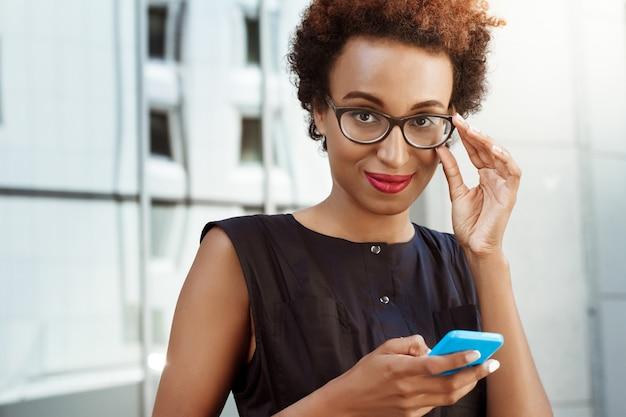Jovem mulher bonita sorrindo segurando o telefone andando pela cidade
