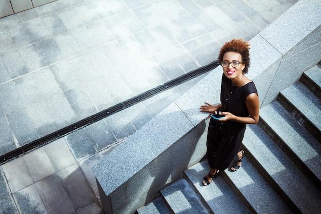Jovem mulher bonita sorrindo segurando o telefone descendo escadas