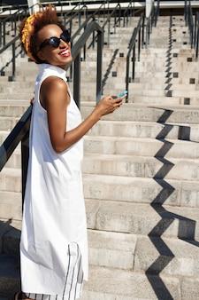 Jovem mulher bonita sorrindo segurando o telefone subindo escadas