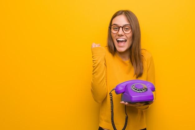 Jovem mulher bonita surpresa e chocada ela está segurando um telefone vintage.