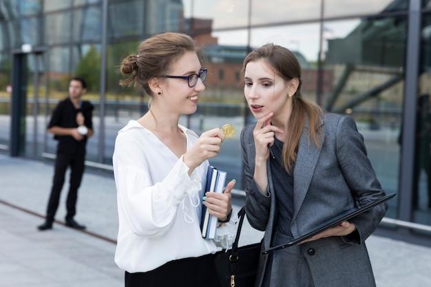Jovem mulher bonita tem bitcoin na mão, tentando explicar ao seu parceiro de negócios que esta é uma direção promissora.