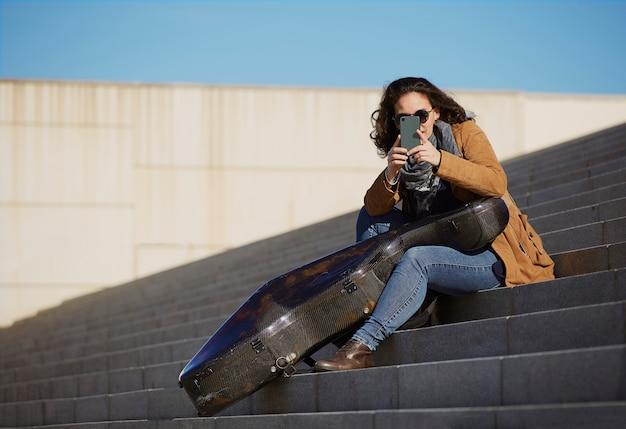 Jovem mulher bonita tirando uma foto com o celular dele.